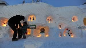 ろうそくの明かりがともされ、雪だるまの姿が浮かび上がる「雪だるままつり」(朝日新聞)